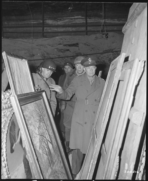 General Dwight D Eisenhower, Supreme Allied commander, inspects art treasures looted by the Germans and stored away in the Merkers salt mine. Behind GEN Eisenhower are General Omar N. Bradley (left), CG of the 12th Army Group, and (right) LT Gen George S. Patton, Jr, CG, 3rd U.S. Army. 4/12/45.