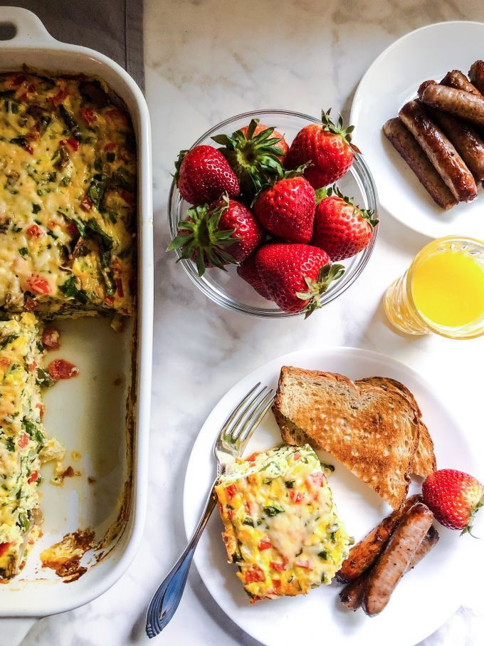This flavorful brunch frittata is packed with fresh veggies and herbs. And, of course, lots of cheese inside and out!  #breakfast #brunch #frittata #vegetarian