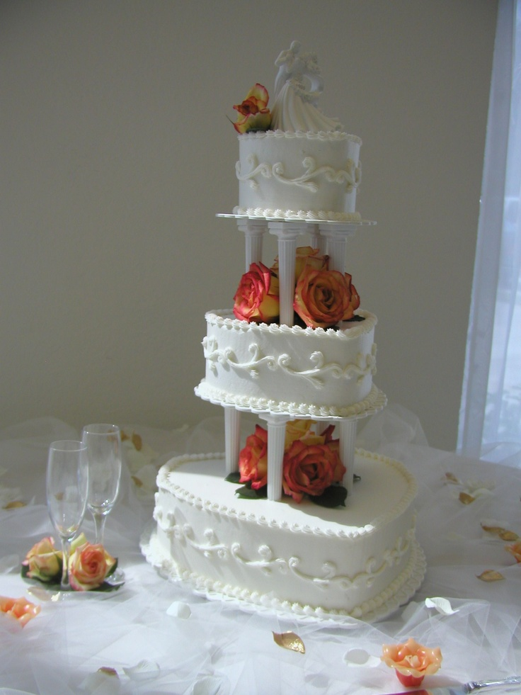 Heartbeat Wedding Cake, buttercream iced heart shaped cakes, scroll designs, orange and yellow roses.  Lakeside Reception Hall, Orlando   www.cakedesigners.net