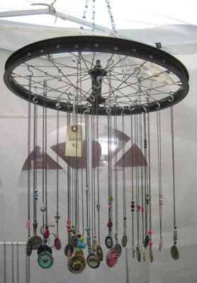 Bike rim suspended from the craft tent and used to hand necklaces.  I saw a few variations on this idea at craft shows last summer.