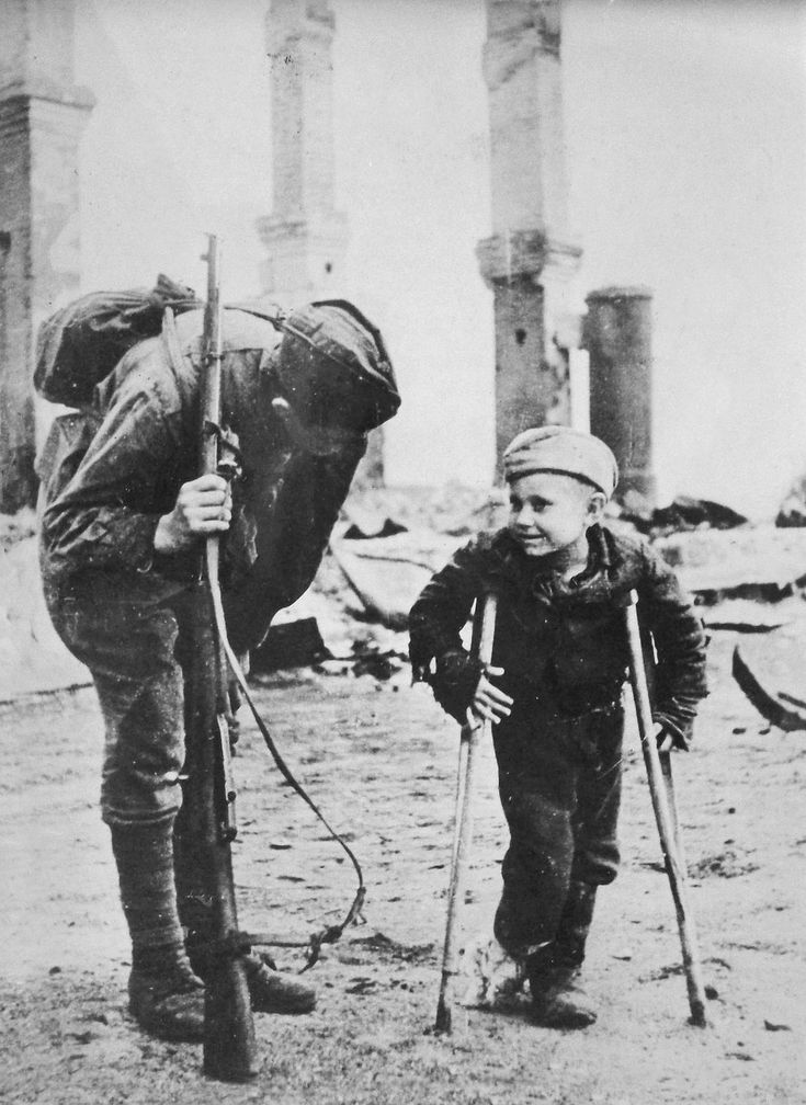 """Young Volodya Lukin talks to a Red Army soldier somewhere in the Baltic region in 1944. Volodya, whose parents were both drafted into the army and was thus left with no home, was exposed to winter cold and lost both of his feet to frostbite -- a little price to pay, according to the original propaganda caption, since his parents belonged to those who """"drove the Germans back to Germany."""""""