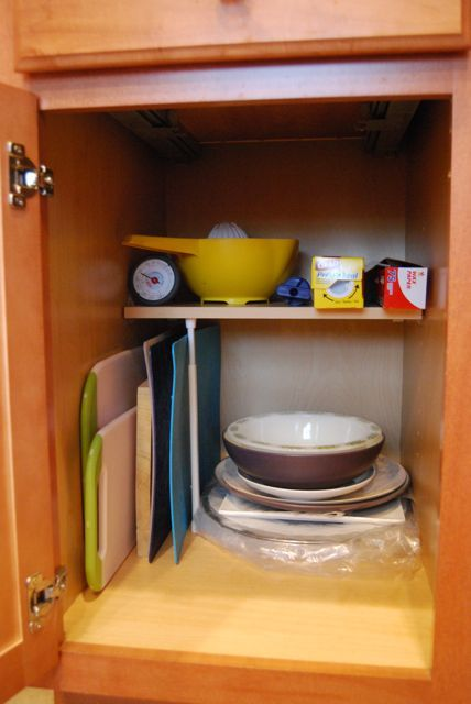 Kitchen Cabinet Cutting Board Storage | The Borrowed Abode; use a tension rod to support cutting boards