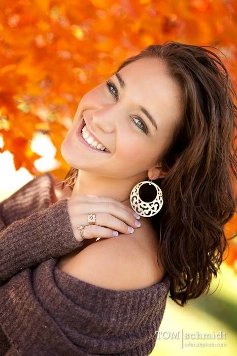 The orange leaves create a nice contrast creating a great background. Wear neutral colors to let your smile steal the show!