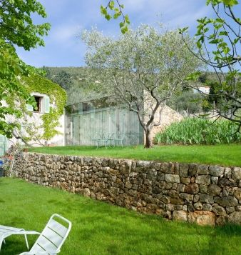 The extension is set within the existing terraced planes, between the main house and the stone walls