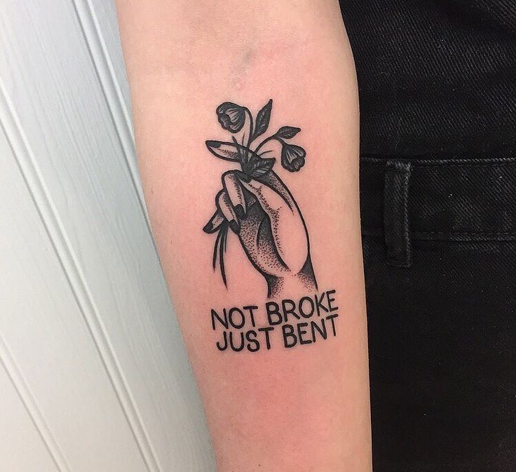 "Black and gray ""not broke just bent"" tattoo with traditional hand holding flowers"