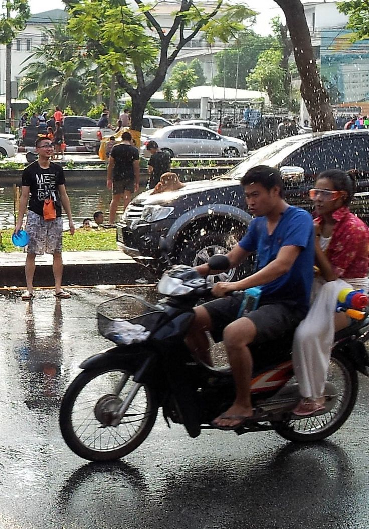 Getting Wet - - - - - Guys on a motorcycle evading water during Songkran. #thailand #travel #photography