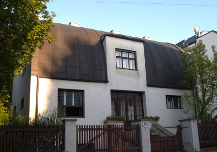 Haus Steiner, Hietzing. Der Auftraggeber hatte den Wunsch, eine Vielzahl von Räumen zu bekommen. Adolf Loos versuchte ein Maximum an Raum zu gewinnen, ohne die Bauvorschriften zu verletzen. Im Hietzinger Villenviertel durften die Häuser straßenseitig nur ein Geschoss über Niveau aufweisen. Über dem Erdgeschoss, äußerstenfalls über dem Hochparterre, musste die Dachzone beginnen. In seiner Lösung wirkt die Straßenfassade eingeschossig, denn über dem Hochparterre wölbt sich bereits das…