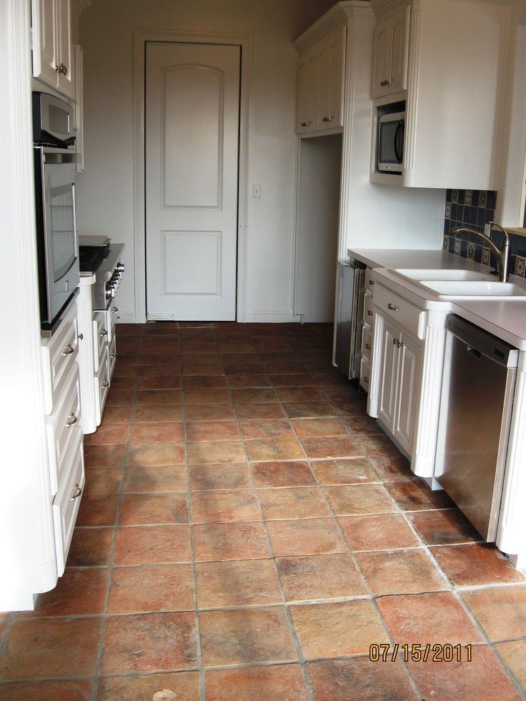 Antique Terracotta Saltillo tile really adds to the appeal of this white classic kitchen