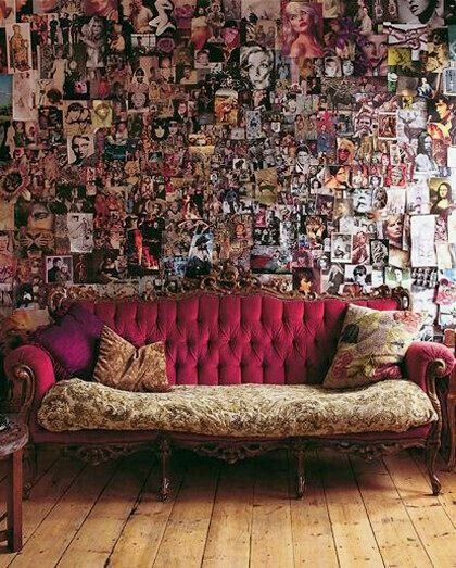 A wall coverd with photographs n a big couch for a fotographr personality