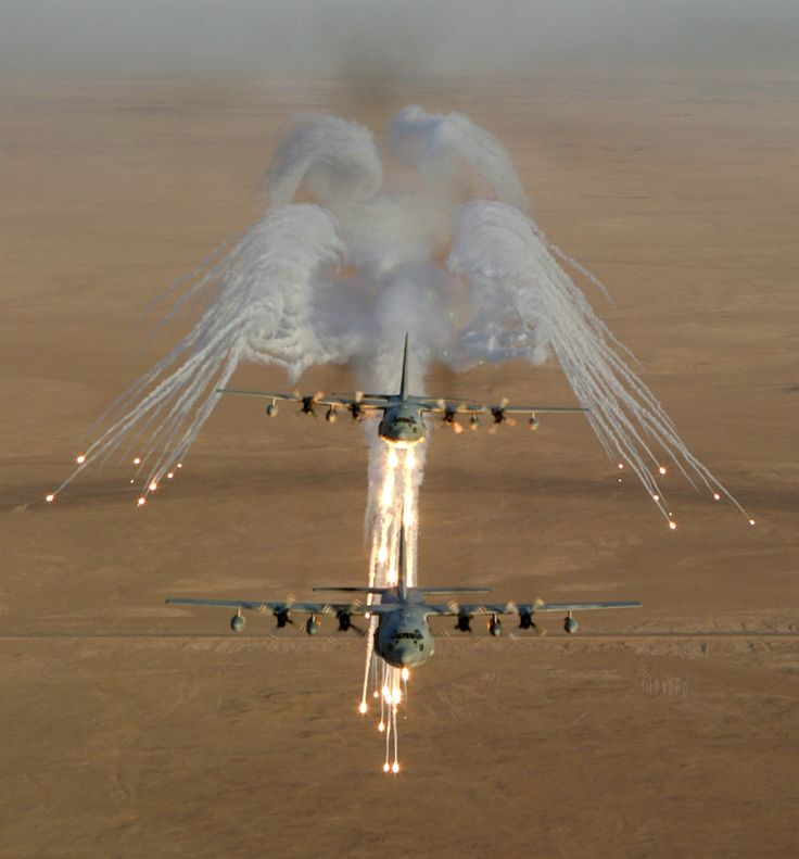 Aerial Photography of Two United States Marine Corps KC-130 Hercules Aircraft, Assigned to Marine Aerial Refueler-Transport - Squadron Two Thirty Four (VMGR-234), Firing Flares That Are Used for Protection Against an Attack by Surface-to-Air Missiles During Operation Iraqi Freedom, September 4, 2003 - Al Jumhuriyah al Iraqiyah – Republic of Iraq