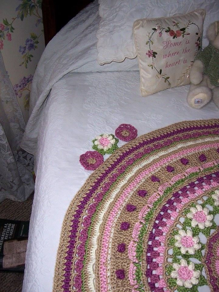 I crocheted four white flowers that matched the flower ring and added one to each of the four corners where the markers were. Then I crocheted eight pink flowers from the center of the mandala pattern to put on either side of the white corner flowers.