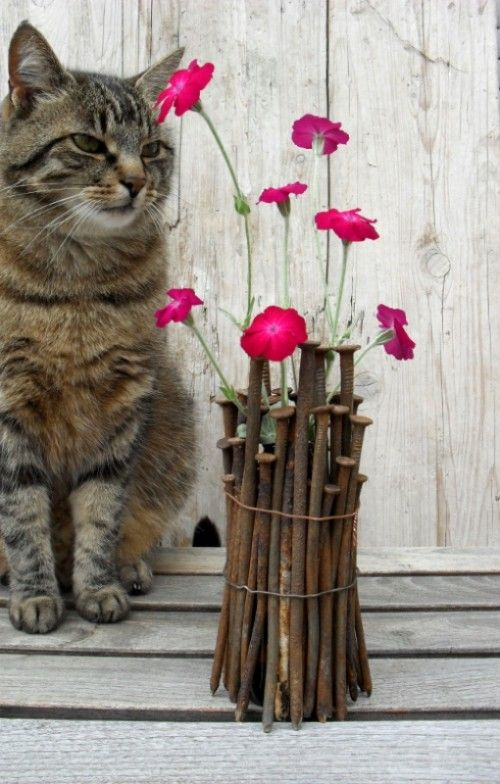 Arrange rusty carpenter's nails around a brown bottle and secure them with two pieces of wire. I love this idea and the kitty.