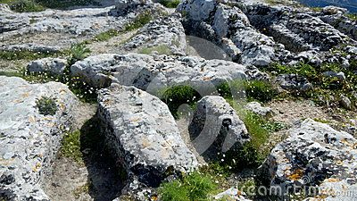 Anthropomorphic graves of unknown origin, carved in stone at the summit of Angelocastro (Castle of the Angel), archaeological site of Byzantine castle on a hilltop overlooking Ionian Sea, Corfu, Greece.