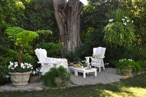 "the rocks serve as a ""rug"" and clearly define the seating space from the landscape.  love, love this idea  I do have a very large pine tree in my back yard     this could work"
