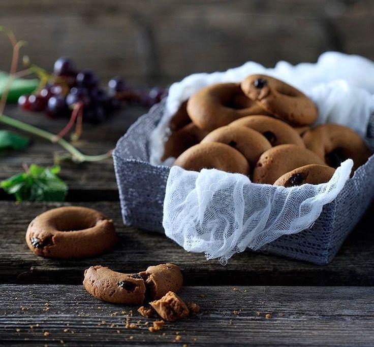 Ανακατεύουμε το μούστο με το ελαιόλαδο, τη ζάχαρη, το κονιάκ και τα μυρωδικά σε ένα μπολ. Περνάμε το αλεύρι με το μπέικιν πάουντερ από κόσκινο. Προσθέτουμε το μείγμα αυτό...