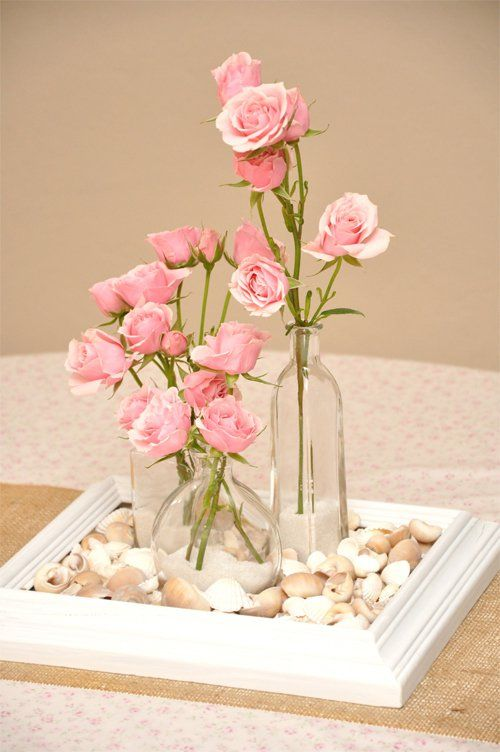 Centerpiece, this looks simple enough. A frame, spray painted to whatever color you want, some filler like rocks or marbles (or confetti!) and vases from the dollar store