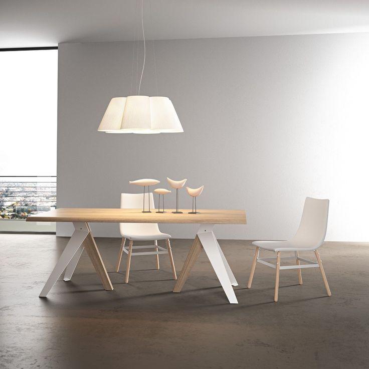 Russel è un tavolo con piano in legno o in vetro e struttura in metallo e legno. Design originale, finiture personalizzabili.
