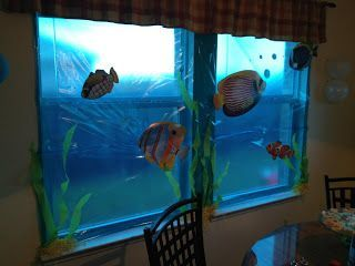 "use blue cellophane to cover windows and add underwater creatures to feel ""under the sea"":"