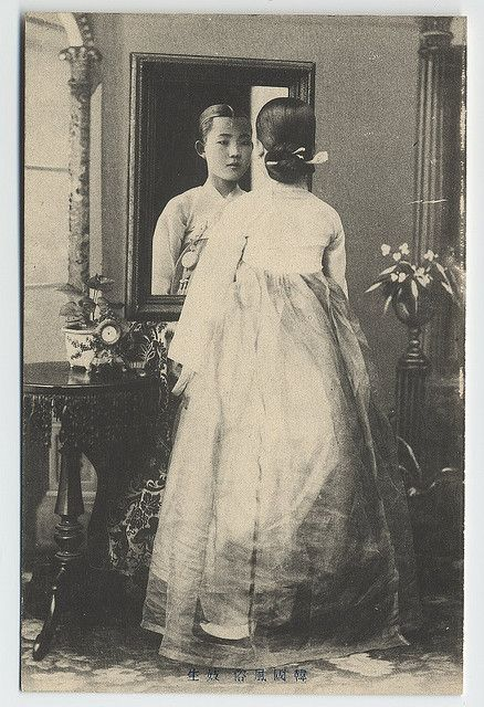 A young 'kisaeng' (singing girl) in full Korean traditional dress. She has a typical married women's hair style (jjok), which is called chignon with a hairpin (the 'pinyo'). Korean 'kisaeng', or singing girls, dressed up for singing and dancing. A 'Kisaeng's' social position was among the lowest in the traditional Korean class system. Their daughters also became 'kisaeng' and their sons became slaves. The art of entertaining of the 'kisaeng' is analogous to the Japanese geisha. These…
