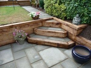 Reclaimed railway sleepers used with block paving to create feature steps in split level garden