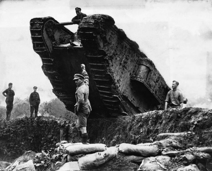 Soldiers maneuver a British tank over a trench during the Battle of Cambrai - this was one of 476 in action. France, 1917.