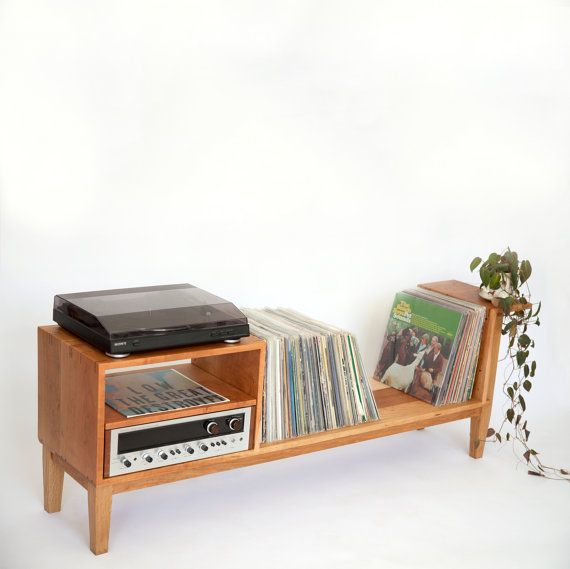 The SIOSI Record Console employs simplistic + democratic design with beautiful details in craft. This piece accommodates a turntable, receiver (the shelf is adjustable), additional component of your choice, and over three-hundred records. Please note the joinery + attention to detail. Solid cherry construction + adjustable shelf // also available in ash or white oak.  62 total width x 14 1/2 depth x 7 off of the ground // Record storage: 35 width x 14 1/2 depth  ...