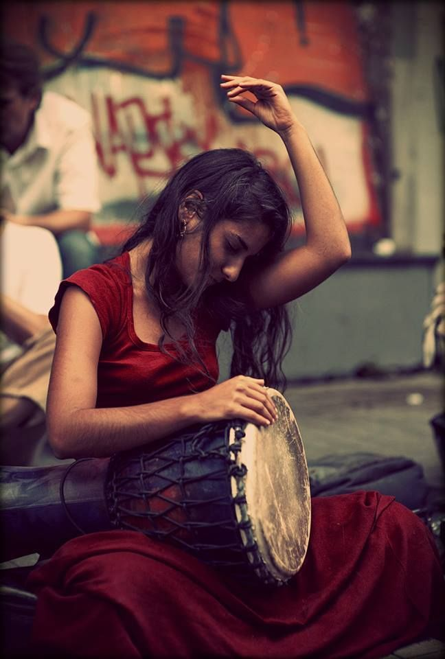 A girl in a red dress playing a djembe hand drum... it may be a klong yao, but I can't see the base length in this great photo...