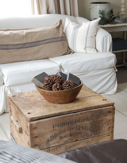 old wooden chest as coffee table, grain sack pillows and white slipcover - farmhouse chic