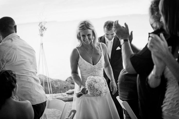 Bride and groom enter the reception at their wedding at home at Milford beach, Auckland. Black and White.  beguiling fine art family photographs for the walls of the most discerning clients homes. We specialise in wedding and family portrait photography, and supply prints on the highest quality media, framed in beautiful conservation standard frames. We are a high end studio located in the beautiful city of Auckland, New Zealand.
