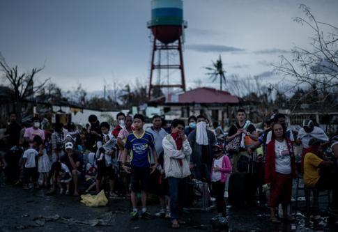 Des survivants du typhon attendent devant l'aéroport de Tacloban, le 12 novembre 2013 - AFP/Philippe Lopez