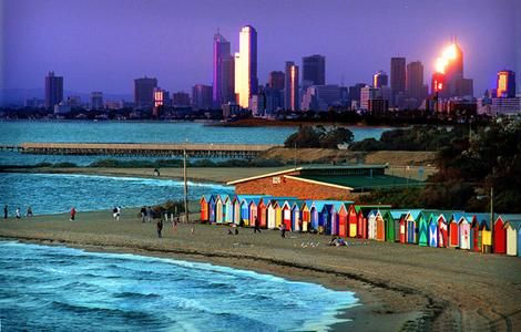 The Melbourne skyline rises behind the colorful bathing boxes on Brighton Beach.