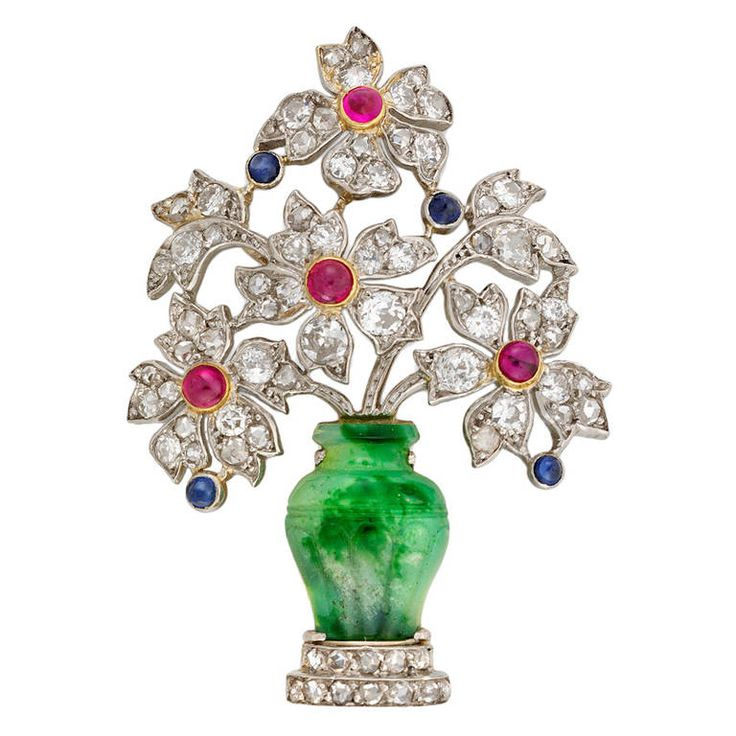 Art Deco Giardinetto Clip. An Art Deco giardinetto clip, the clip comprising a jade vase with two-tiered rose-cut diamond base, the vase set with diamond-set flowers, estimated to weigh a total of 1.60 carats, embellished with cabochon-cut rubies and sapphires, all set in platinum with pin fitting, gross weight 8.5 grams, circa 1930