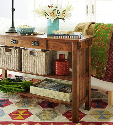 Give an old table a new look. Transform a console table from a surface where clutter gathers into a functional table packed with storage opportunities. Two big baskets hold coffee table books, while a throw and a box of games rest on the bottom shelf. Remotes and spare keys go in the small top drawer.  Could use this as divider between front hall and living room.