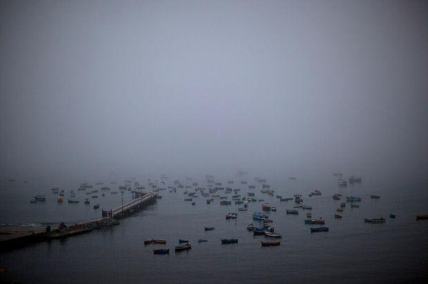 Πρωινή ομίχλη, ακτή Ειρηνικού, μικρές αραγμένες ψαρόβαρκες.Lima, Peru.
