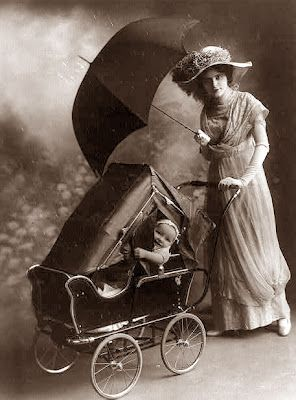 This picture was taken in 1913, and it shows a woman with a baby stroller and an umbrella. She is also wearing a very fancy hat.