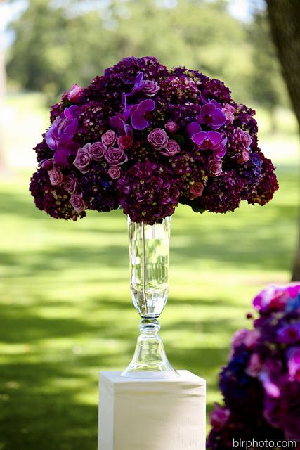Wow! Various hues of purple in this tall centerpiece are so regal looking. This is just beautiful. I can only imagine how many people will want this piece for their event after seeing it. Stunning!
