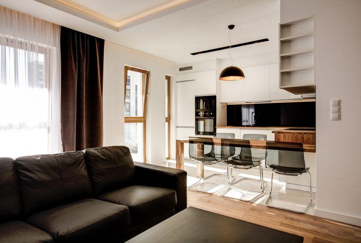Kącik jadalniany, który stanowi granicę pomiędzy salonem a kuchnią. Drewniany stół i plastikowe krzesła to bardzo nowoczesne rozwiązanie.