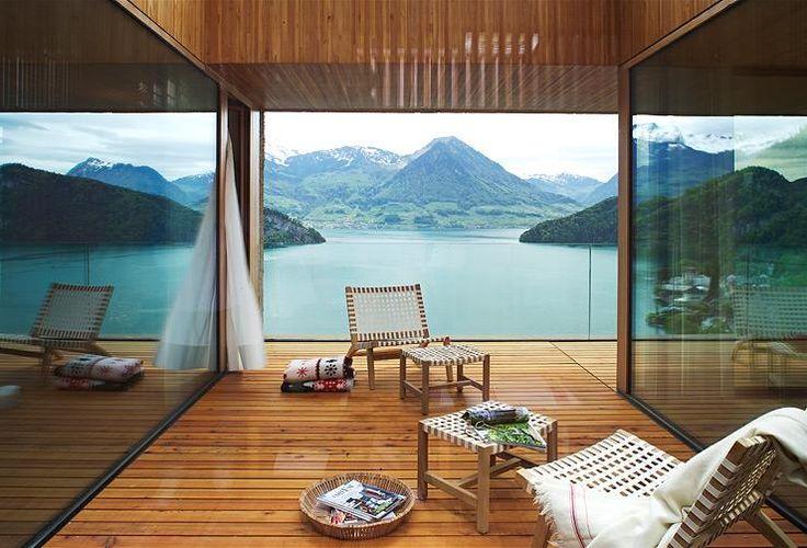 Am Vierwaldstätter See in der Schweiz hat Architekt Daniel Lischer ein Holzhaus in Beton gehüllt. Loggien und große Fenster machen sein Lärchenkern sichtbar.