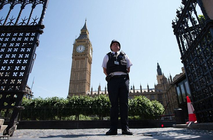A policeman outside the Houses of Parliament, where flags were flown at half mast today in remembrance of those who were killed