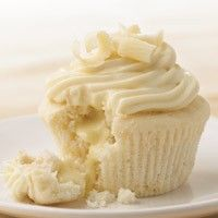 White Chocolate Cupcakes with Truffle Filling - just as they come out of the oven you snip the top of the cupcake and press a Lindt Truffle in the hot cupcake. Yum