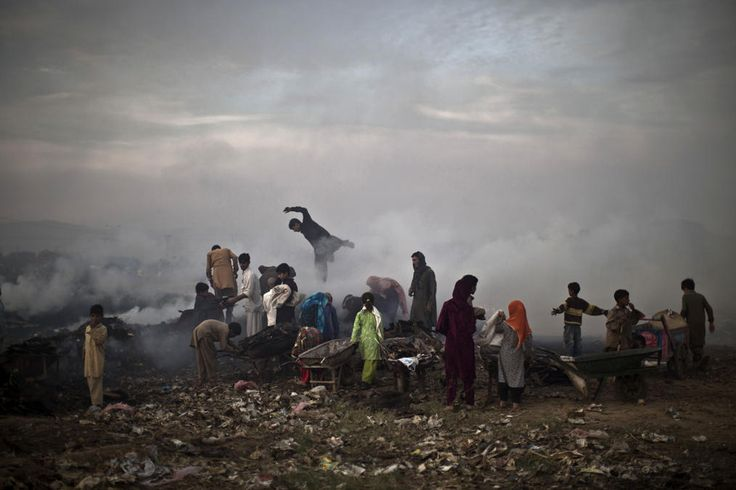 Pakistan daily life -- Pakistanis, survey woods from a burning field, which was used by fruit and vegetable sellers to store their wooden boxes, on the outskirts of Islamabad, Pakistan, Monday, Nov. 4, 2013. According to the crowds at the site, the Capital Development Authority burned the field because it was used by the sellers to store their wooden boxes illegally. (AP Photo/Muhammed Muheisen)