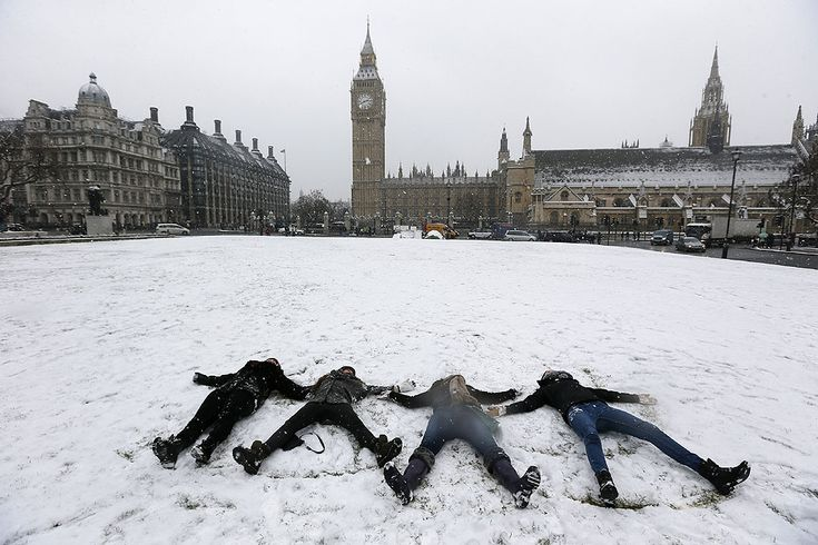 Four youths make snow angels in Parliament Square next to the Houses of Parliament in central London.