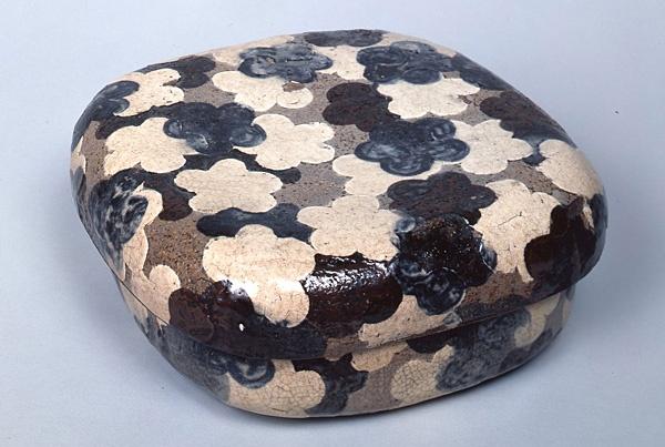 「光琳文様」銹絵染付梅花散文蓋物 尾形乾山 江戸時代 18世紀 光琳や乾山など、琳派の作家達による、動植物や自然を大胆にデザイン化した文様は、総称して光琳文様と呼ばれる。梅は古くから日本人に愛好され、文様として様々な場面で使用されるが、これは型紙を使って、梅花のシルエットのみを大胆に表現している。白、紺、茶の三色で表された梅花が重なりあうように配されて、日本的情緒あふれる意匠である。