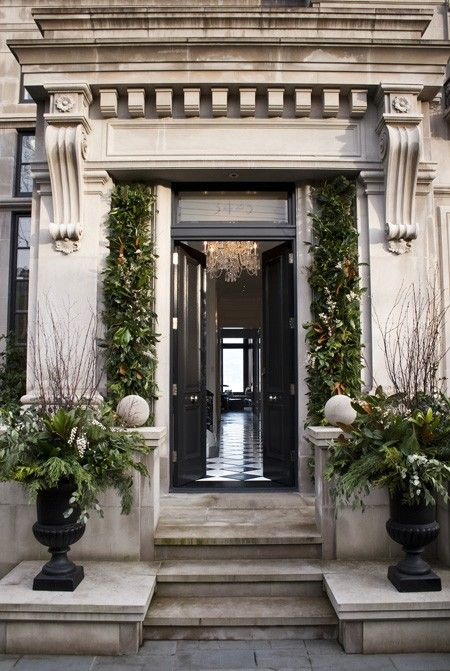 Large black urns filled with seasonal greenery and branches make a statement. Garlands incorporating green, white and rust colours decorate the front doorPhotographer: Kim Christie
