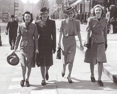 The woman on the far right is wearing an Eisenhower jacket from the 1940s. This jacket was based on military jackets that were slightly bloused above the waist and gathered to a fitted belt at the waist.