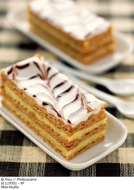 "The mille-feuille (""thousand sheets""), vanilla slice, custard slice, also known as the Napoleon, is a pastry of French origin. Traditionally, It's made up of three layers of puff pastry, alternating with two layers of pastry cream, but sometimes whipped cream, or jam are substituted. The top pastry layer is dusted with confectioner's sugar, and sometimes cocoa, or almonds. Alternatively the top is glazed in alternating white and chocolate stripes, and combed."