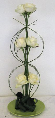 White rose grouped arrangement, with folded aspidistra leaves and steel grass