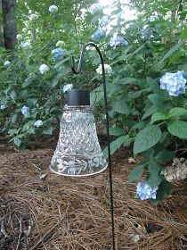 DIY:  How to Make a Garden Light - using an old glass globe, wire, a a $1 solar light and a shepherd's hook. This post also shows how to make the wire  hanger.  This is clever use of vintage glass globes - via Shanty Insanity!