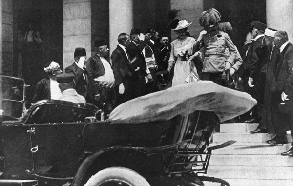 """...In this photo, taken in Sarajevo on June 28, 1914, a visiting Archduke Franz Ferdinand and his wife, Czech Countess Sophie Chotek, are departing a reception at City Hall. Earlier that morning, on the way to the hall, their motorcade had been attacked by one of a group of Serbian nationalist assassins, whose bomb damaged one car and injured dozens of bystanders. After this photo was taken, the Archduke and his wife climbed into the open car, headed for a nearby hospital to visit the…"