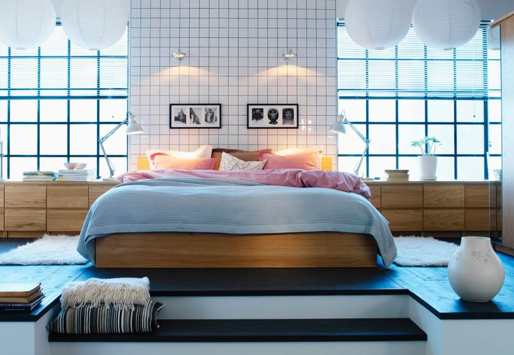 A modern bedroom with a large white bed on a podium under white lanterns and next to light wood storage